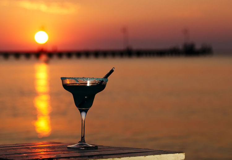 Alcohol Alcoholic Drink Beach Beverage Cocktail Colorful Drink Glass Light Nature Nobody Ocean Orange Outdoors Sea Sun Sunset Tropical Water
