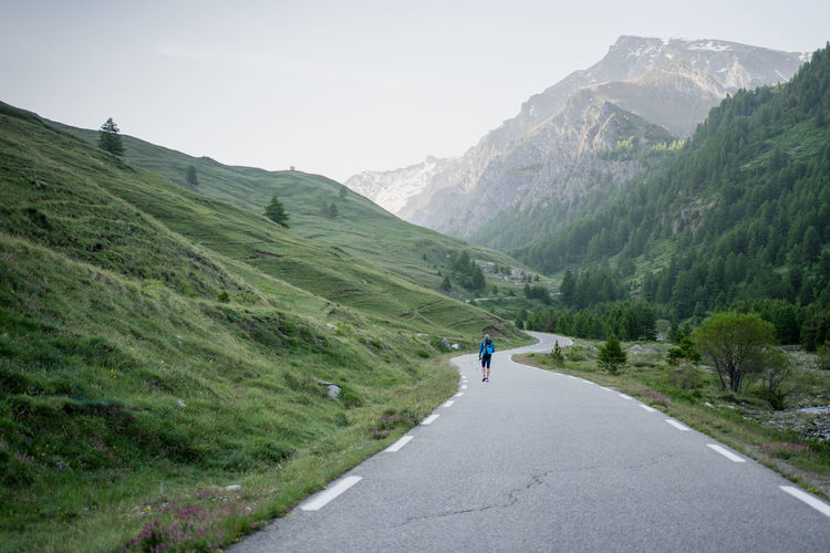 Rear view of person on road amidst mountains against sky