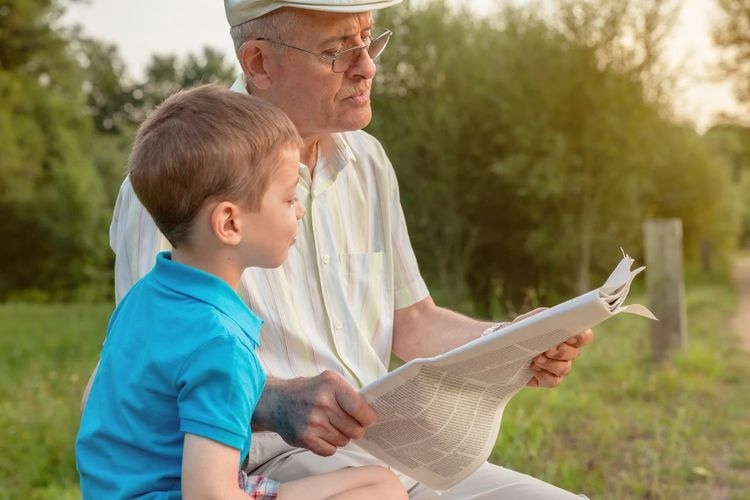Closeup of senior man and cute child reading a newspaper sitting over a nature background. Two different generations concept. Detail Relax Mature Cute Caucasian Age Hat Parent Complicity Together Education Sitting Male Adult Background Blurred Defocused Smiling Happy Leisure Lifestyle Old People Real Two Elderly Nature Family Learning Teaching Generation Closeup Outdoors Grandparent Grandfather Grandchild Grandson Park Bench Looking Reading Paper News Newspaper Boy Kid Child Man Senior