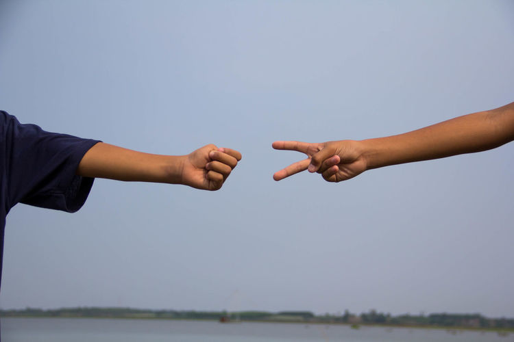 Cropped image of people hands gesturing against clear sky