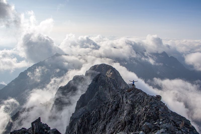 Person standing on mountain against cloudy sky