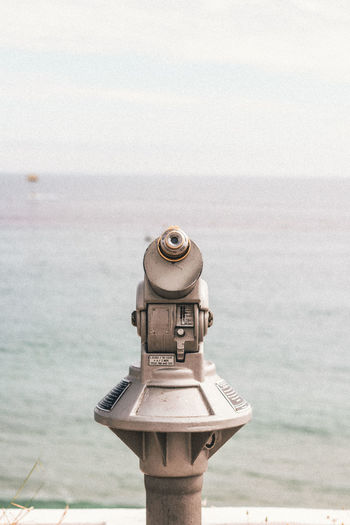 Close-up of coin-operated binoculars on sea against sky