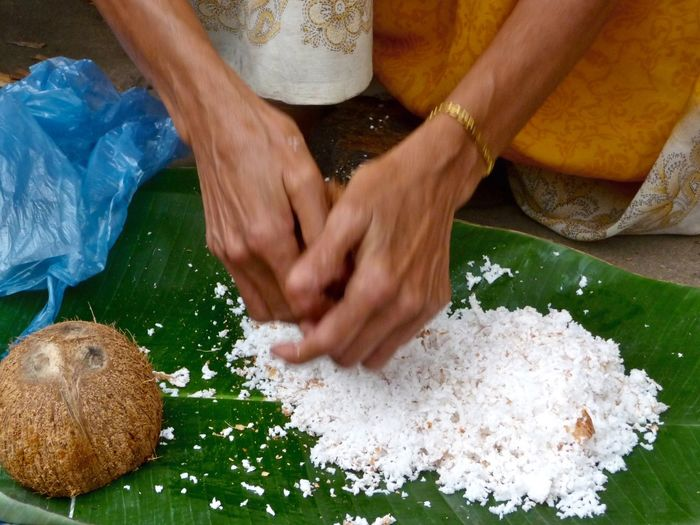Cropped hands of woman grating coconut