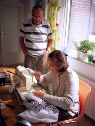 Senior Woman Sewing Textile On Machine While Sitting By Man