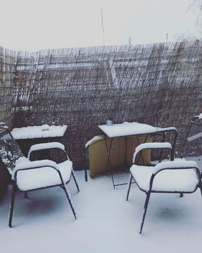 Empty chairs against snow covered wall and buildings during winter