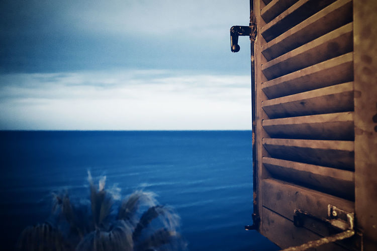 Through The Window Night Nightphotography Alassio Liguria Italy Palmtree Water Sea Ocean Sky Horizon Horizon Over Water Nature Cloud - Sky Beauty In Nature No People Scenics - Nature Day Tranquil Scene Outdoors Tranquility Wood - Material Idyllic Built Structure Metal Nautical Vessel