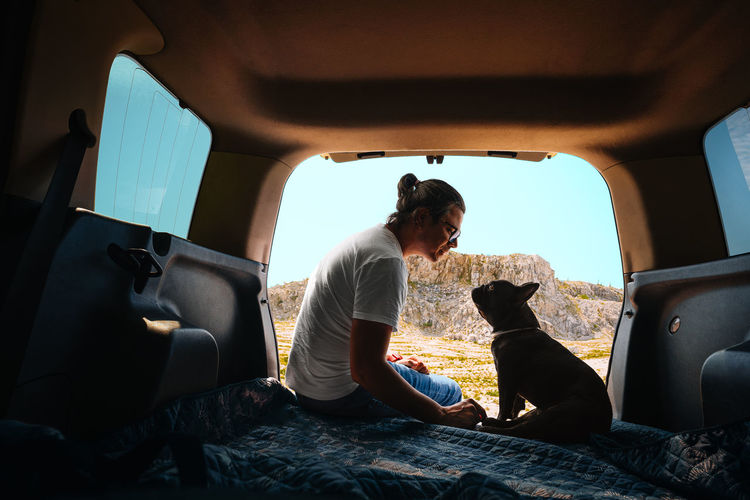 Man and french bulldog sitting and bonding in car trunk