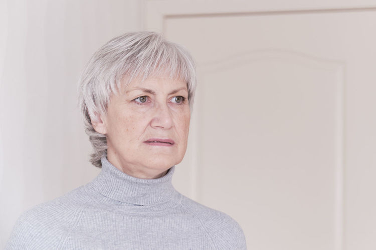 Portrait of mid adult woman against wall