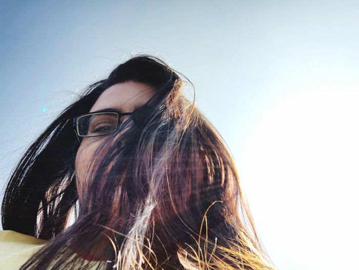 Low angle portrait of woman with long hair against bright sky