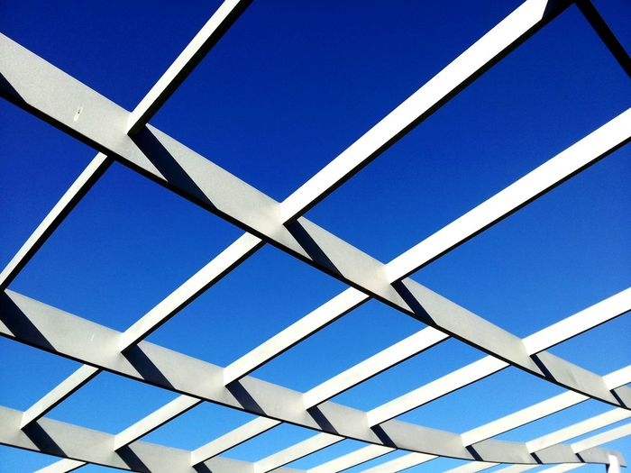 Low angle view of silver roof beam against clear blue sky