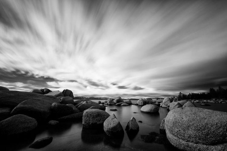 Cloudy sky above rocky stream