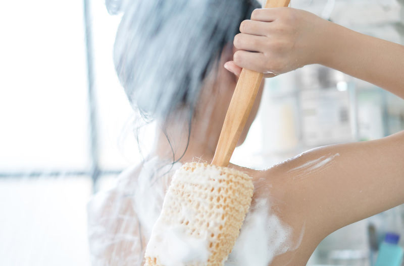 Close-Up Of Shirtless Woman Scrubbing Back In Bathroom