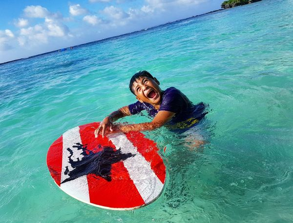 Outdoors Leisure Activity Sea Beach Smiling Happytime The Blue Sea Happy Beautiful Sky Beach Day Skimboard Sun Family Clouds