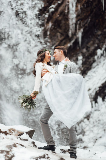Couple kissing in snow during winter