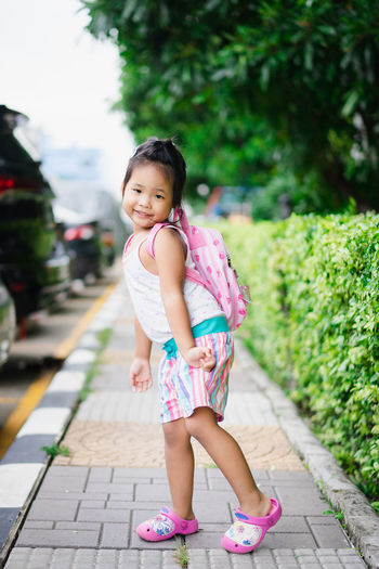 Portrait Of Cute Girl With Backpack Posing On Footpath
