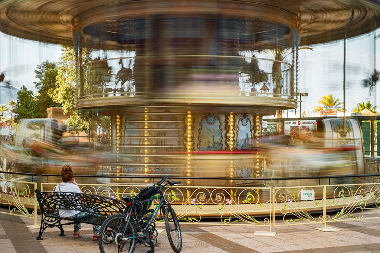 the moving carousel and the woman sitting on the bench next to a bicycle Carousel Moving Bycicle Blurred Motion Motion Speed Transportation City Real People Architecture Sitting Mode Of Transportation Seat on the move Women People Adult Men Leisure Activity Day Lifestyles Long Exposure Outdoors The Art Of Street Photography My Best Photo