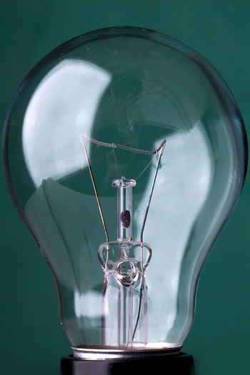 Close-Up Of Light Bulb Against Green Background