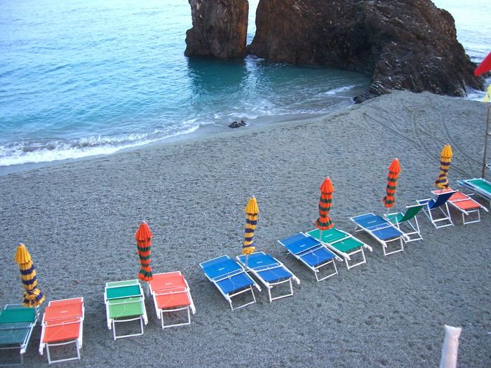 High Angle View Of Colorful Lounge Chairs And Closed Parasols At Beach