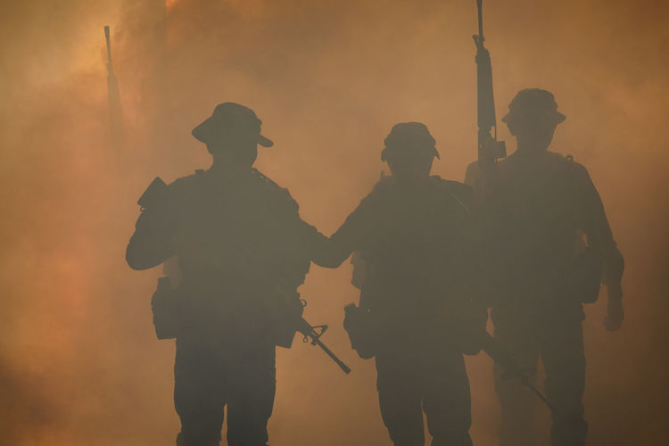 Silhouette army soldiers walking against smoke at night