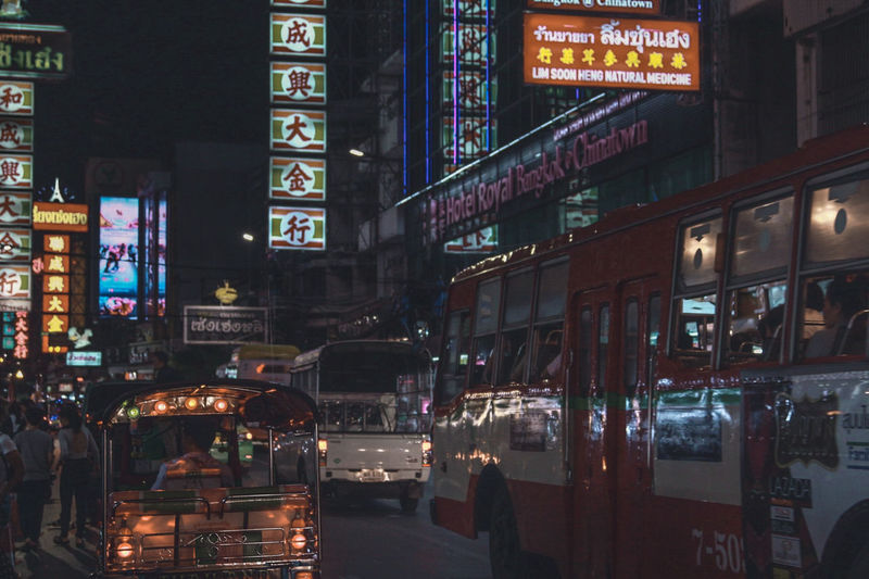 Buses on road in city at night