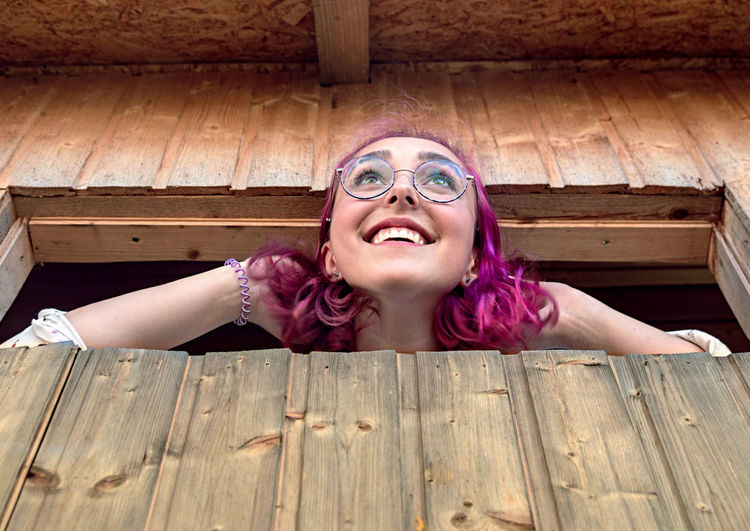 Portrait of happy woman lying on wooden floor
