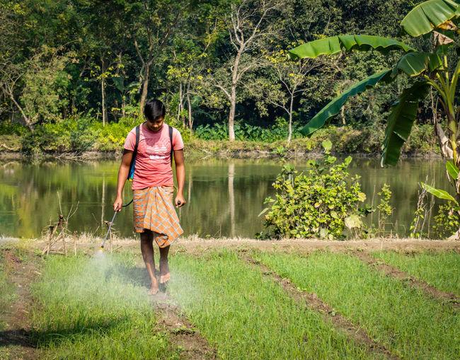 Rear view of man walking by lake