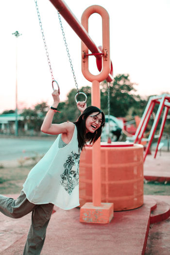 Full length portrait of woman standing on swing at playground