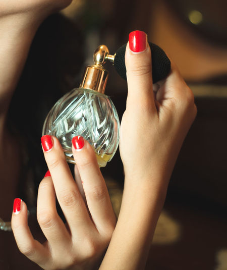 Close-up of woman holding perfume sprayer
