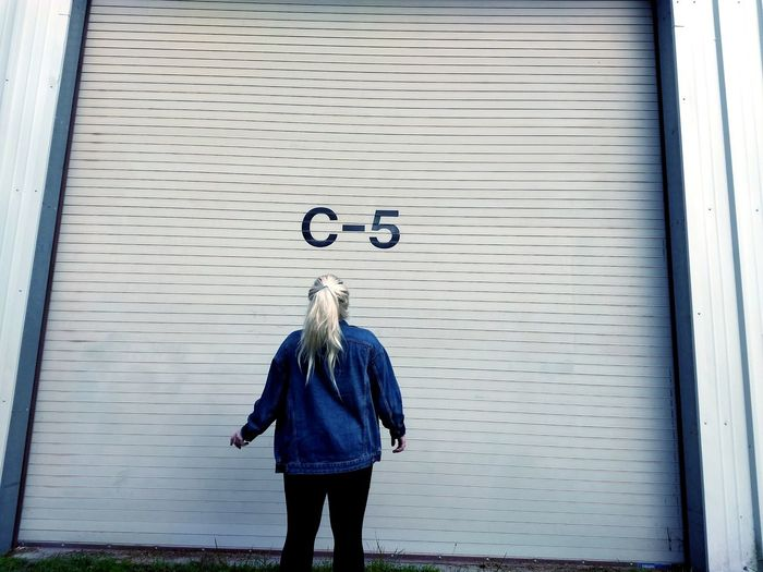Rear view of woman standing against closed shutter