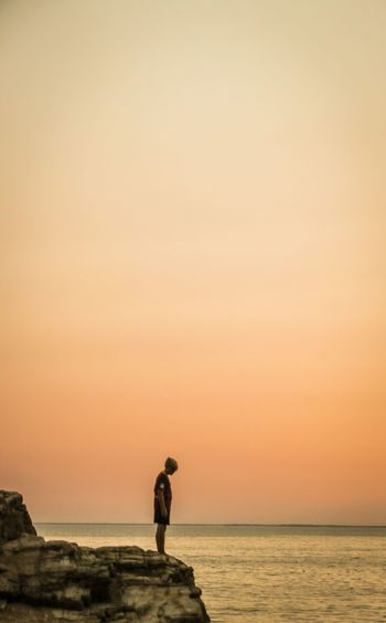 Side view of mature man standing on rock by sea against sky during sunset