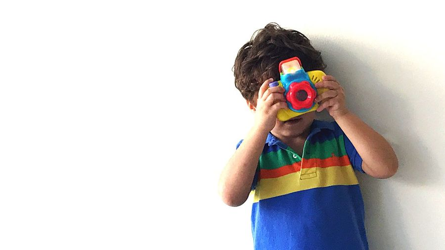 Boy playing with multi colored background