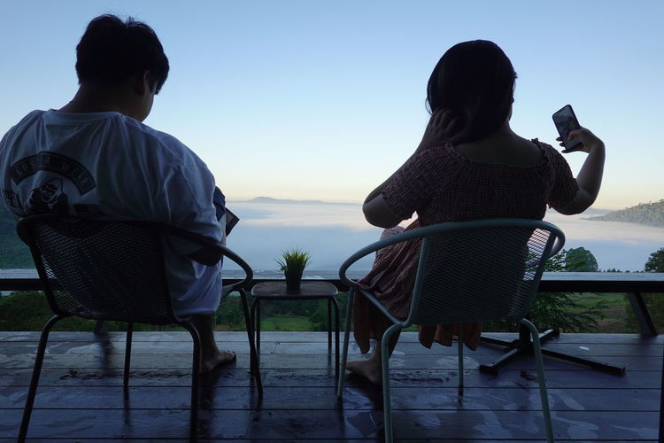 Rear view of couple sitting on chair by sea against sky