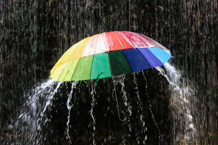 Close-up of water drops on multi colored umbrella