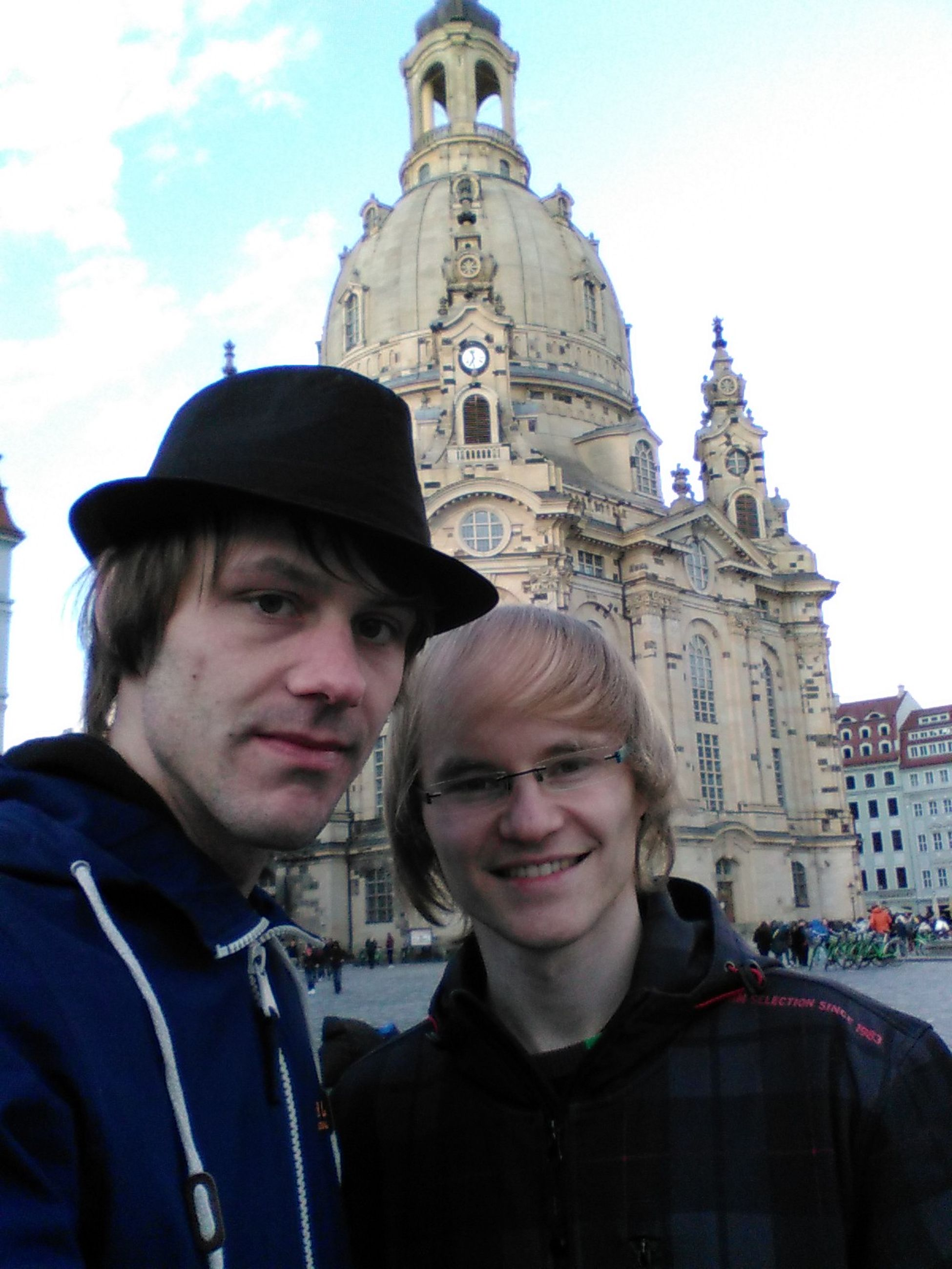 two people, real people, lifestyles, headshot, looking at camera, young men, mid adult men, togetherness, portrait, mid adult, men, sky, leisure activity, standing, architecture, love, outdoors, building exterior, day, couple - relationship, front view, bonding, young adult, built structure, low angle view, smiling