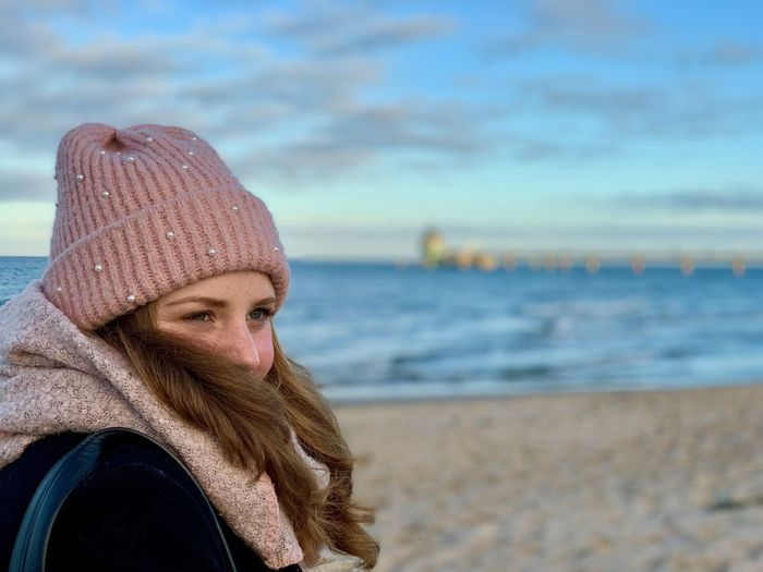 Portrait of woman wearing hat against sea during winter