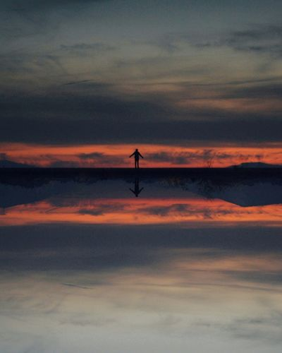 Reflection of silhouette boy in lake against sky during sunset