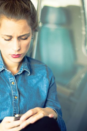 Close-Up Of Young Woman Sitting In Train