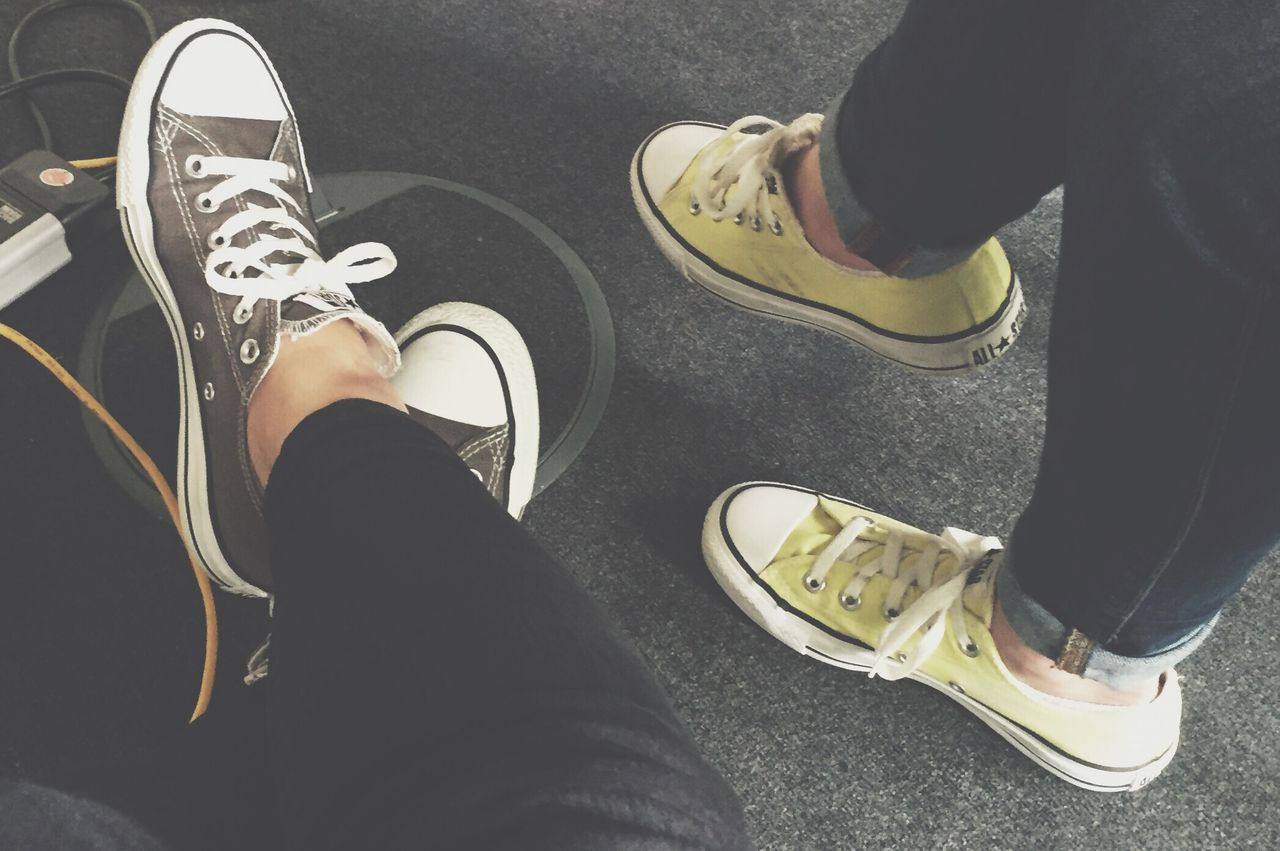 low section, human leg, shoe, human body part, high angle view, human foot, canvas shoe, two people, real people, personal perspective, standing, shoelace, men, lifestyles, pair, leisure activity, road, togetherness, day, indoors, close-up, adult, people