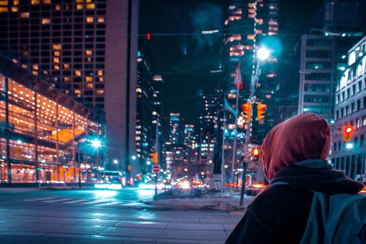 Rear view of man on illuminated city street at night