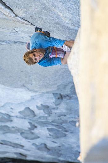 Portrait of man climbing on rock