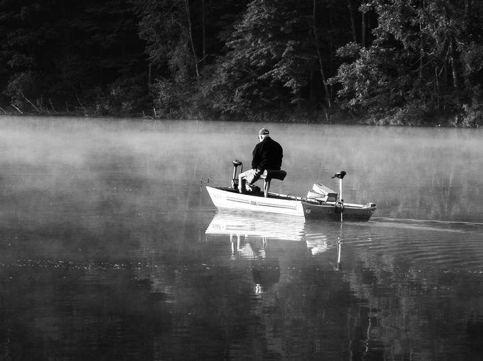 Rear view of man sitting on fishing boat at lake