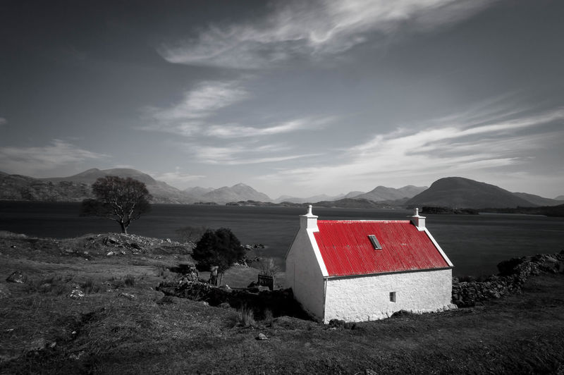 View Of Lone House On Riverbank Against Cloudy Sky