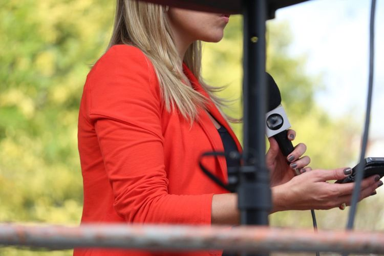A TV station reporter working Casual Clothing Comunication Day Holding Interview Microphone Midia Outdoors Part Of Person Public Transportation Women
