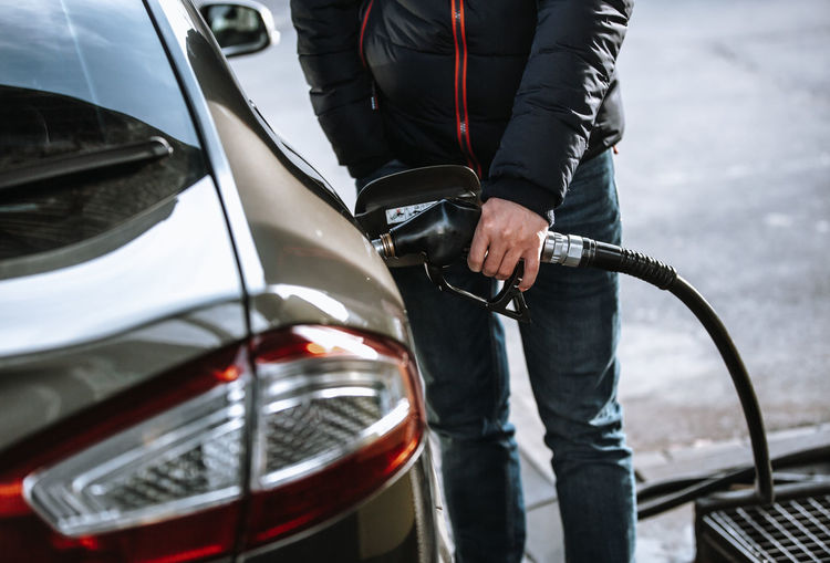 Midsection of man refueling car