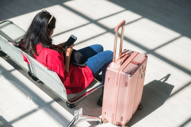 Rear view of woman sitting at airport