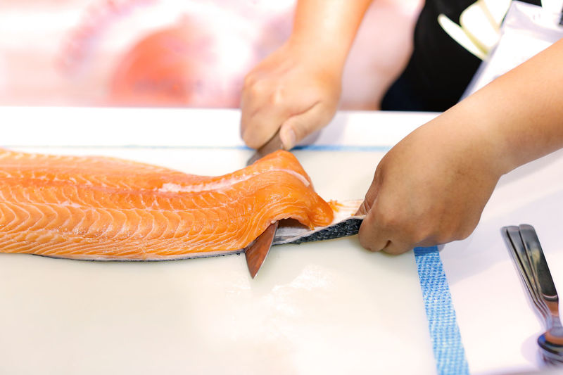Cropped hands of chef cutting fish in commercial kitchen
