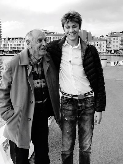Happy Grandfather And Grandson Standing Against Sky In City