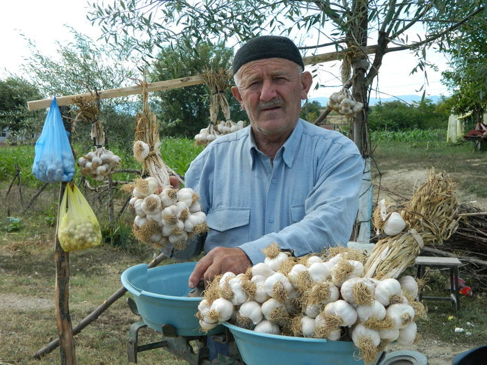 Portrait of senior man selling garlic