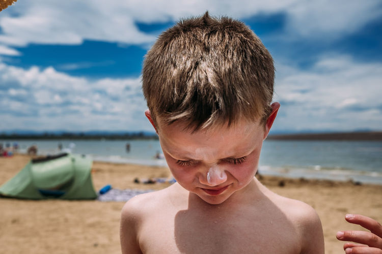 Portrait of shirtless boy at beach against sky