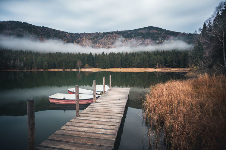 Water Lake Tranquility Tranquil Scene Scenics - Nature Beauty In Nature Sky Reflection Nature No People Non-urban Scene Tree Cloud - Sky Mountain Wood - Material Nautical Vessel Pier Idyllic Outdoors Peer Boat Boats Fall Beauty Floating On Water Reflection